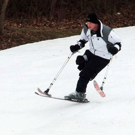 A male amputee using the 3-tracker to ski.