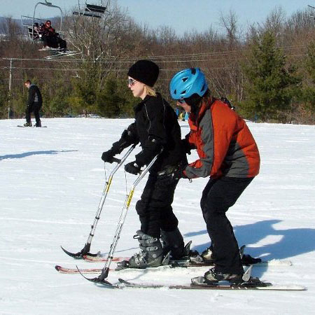 An instructor helping a student who is skiiing with a 4-tracker.
