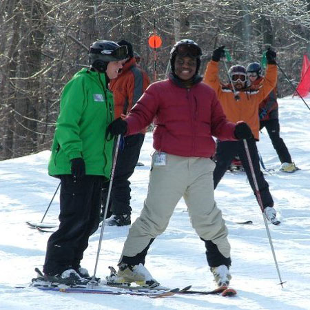 A smiling African American boy on skis standing next to a guide.