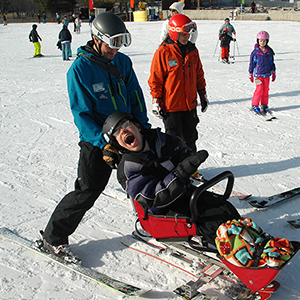 A male sit-down skier laughing as he is pushed in a mono ski by a volunteer..