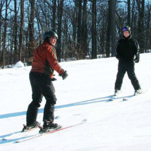 An instructor stand-up skiing backwards in front of a student for face-to-face interaction.
