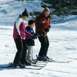 A young stand-up skier and two volunteers hold a bamboo pole as they ski.