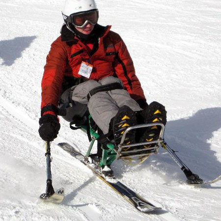 An instructor on a mono ski holding outriggers.