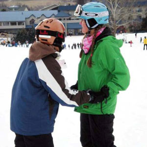 Student and volunteer snowboarders demonstrating doing the dance—face to face and holding hands to help with balance.