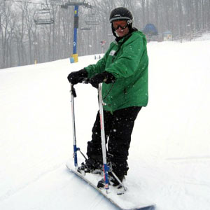 A male snowboarding with the rider bar attached to the snowboard.