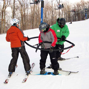 Two volunteers help a snowboard student get into a Sno-wing.