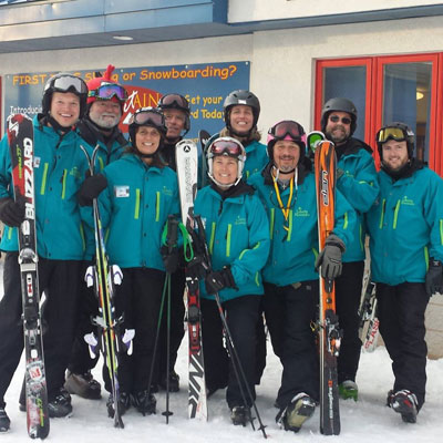 Nine volunteer ski instructors holding their skies beside them, all in the uniform blue jacket of the Blue Ridge Sports Center, stood posing for a group photo.