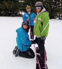 A male snowboarder standing with two instructors holding a tether behind him..